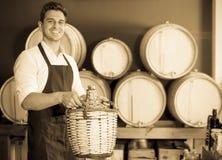 Vendedor alegre do homem que guarda a garrafa de vime grande com vinho Imagem de Stock Royalty Free