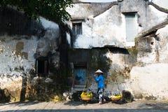 Vendedor ambulante perto da parede velha em Hoian, Vietname Foto de Stock