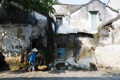 Vendedor ambulante perto da parede velha em Hoian, Vietname Fotos de Stock Royalty Free