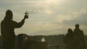 Vendedor ambulante que hace burbujas de jabón coloridas grandes con la máquina del juguete en la cámara lenta metrajes