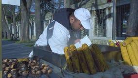Vendedor ambulante que vende el maíz en la mazorca asado a la parrilla almacen de video