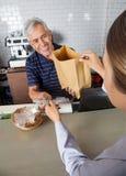 Vendedor Collecting Cash While que pasa el bolso de ultramarinos Fotografía de archivo libre de regalías