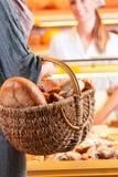 Vendedor con el cliente femenino en panadería Fotografía de archivo