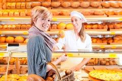 Vendedor con el cliente femenino en panadería Foto de archivo libre de regalías