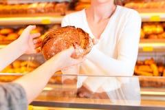 Vendedor con el cliente femenino en panadería Fotos de archivo libres de regalías