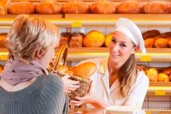 Vendedor con el cliente femenino en panadería Imagenes de archivo