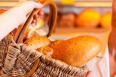 Vendedor con el cliente femenino en panadería Foto de archivo
