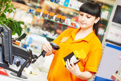 Vendedor con el escáner del código de barras en tienda Fotos de archivo
