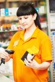 Vendedor con el escáner del código de barras en tienda fotografía de archivo libre de regalías