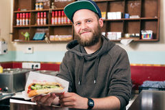 Vendedor con el perrito caliente en snack bar de los alimentos de preparación rápida Foto de archivo libre de regalías