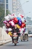 Vendedor con los globos en una e-bici, Pekín, China Imagen de archivo