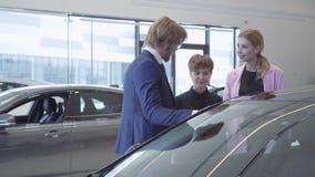 Vendedor confiado en el traje y dos clientes femeninos que hablan cerca del coche moderno Mujeres que eligen el vehículo que cons almacen de metraje de vídeo