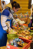 Vendedor da menina sobre o contador com as casas de pão-de-espécie encaracolado Foto de Stock Royalty Free