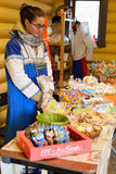Vendedor da menina sobre o contador com as casas de pão-de-espécie encaracolado Imagens de Stock Royalty Free