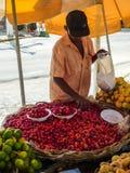 Vendedor da tenda do mercado de rua que escolhe algum acerola das cerejas de Barbados para vender imagens de stock
