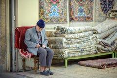 Vendedor de alfombras en el mercado de Isfahán fotos de archivo libres de regalías
