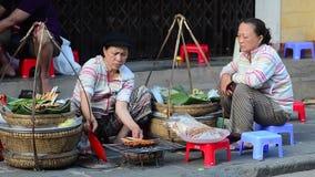 Vendedor de alimento da rua que prepara o alimento que senta-se no passeio video estoque