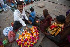Vendedor de calle en los bancos del río Ganges sagrado que vende los pétalos de la flor Foto de archivo libre de regalías