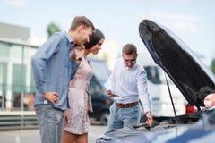 Vendedor de carro no negócio que mostra o motor a um cliente fotografia de stock royalty free