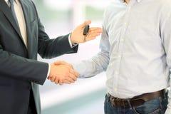 Vendedor de carro que cede as chaves para um carro novo a um homem de negócios novo Aperto de mão entre dois executivos Foco em u Imagens de Stock