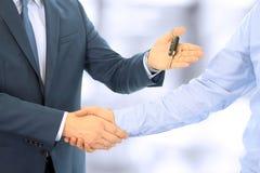 Vendedor de carro que cede as chaves para um carro novo a um homem de negócios novo Aperto de mão entre dois executivos Foco em u Foto de Stock
