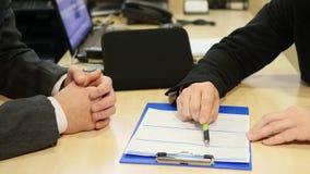 Vendedor de coches profesional que muestra los papeles para firmar a su cutomer Hombre hermoso joven que se prepara para firmar d almacen de video
