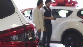 Vendedor de coches profesional que muestra los coches para la venta a su cliente masculino metrajes
