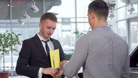 Vendedor de coches que da llaves del coche al cliente después de sacudir las manos almacen de video