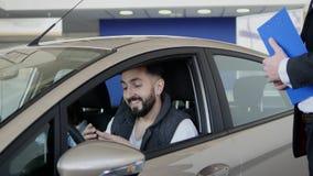 Vendedor de coches que entrega las llaves para un nuevo coche almacen de metraje de vídeo