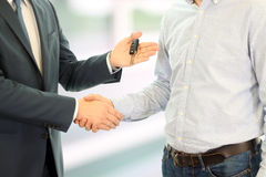 Vendedor de coches que entrega las llaves para un nuevo coche a un hombre de negocios joven Apretón de manos entre dos hombres de Imagenes de archivo