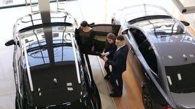 Vendedor de coches que habla con los clientes en la sala de exposición y las demostraciones ellas un nuevo coche almacen de metraje de vídeo
