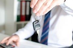 Vendedor de coches que lleva a cabo una llave Imágenes de archivo libres de regalías