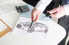 Vendedor de coches que muestra un diseño del coche Foto de archivo libre de regalías