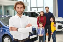 Vendedor de coches y familia borrosa cerca del auto imagen de archivo