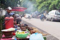 Vendedor de comida de la calle en Luang Prabang, Laos, vendiendo las carnes asadas a la parrilla en un palillo y otras comidas tr imagenes de archivo