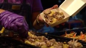 Vendedor de la cámara lenta preparar los huevos de una codorniz fritos deliciosos con los pequeños pulpos almacen de video