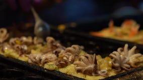 Vendedor de la cámara lenta preparar los huevos de una codorniz fritos deliciosos con los pequeños pulpos almacen de metraje de vídeo