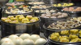 Vendedor de la cámara lenta que vende la bola de masa hervida y Shaomai en mercado asiático de la comida de la calle metrajes