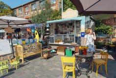 Vendedor de la comida rápida y de las bebidas en el café móvil al aire libre durante festival de la comida de la calle Foto de archivo