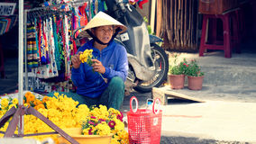 Vendedor de la flor de la calle en Hoi An fotos de archivo