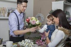 Vendedor de la flor con la madre y el niño Imagenes de archivo
