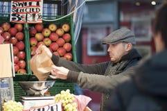 Vendedor de la fruta que envuelve para arriba las frutas, Londres, Reino Unido, 2011 Foto de archivo