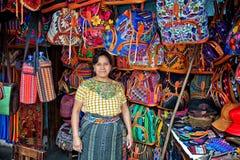 Vendedor de la mujer con los productos hechos a mano en su parada del mercado foto de archivo libre de regalías