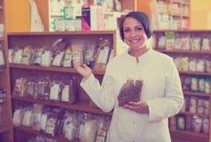 Vendedor de la mujer que sostiene productos de las pastas Imagen de archivo libre de regalías