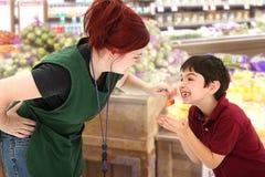 Vendedor de la tienda de comestibles que da cerezas del niño en almacén Fotografía de archivo libre de regalías
