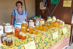Vendedor de las mujeres de la miel en el mercado de los granjeros Foto de archivo libre de regalías