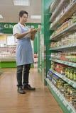 Vendedor de las ventas que comprueba mercancía en supermercado Foto de archivo libre de regalías