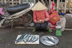 Vendedor de los pescados que cuenta el dinero en el mercado callejero Vietnam