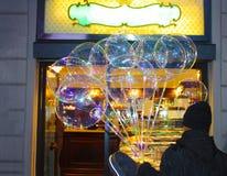 Vendedor de muchos globos transparentes delante de una tienda brillante del partido foto de archivo