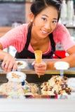 Vendedor de sexo femenino en sala con el cono de helado Imagen de archivo